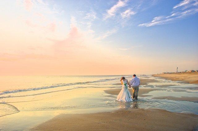 New couple walking on the beach at sunrise after their wedding